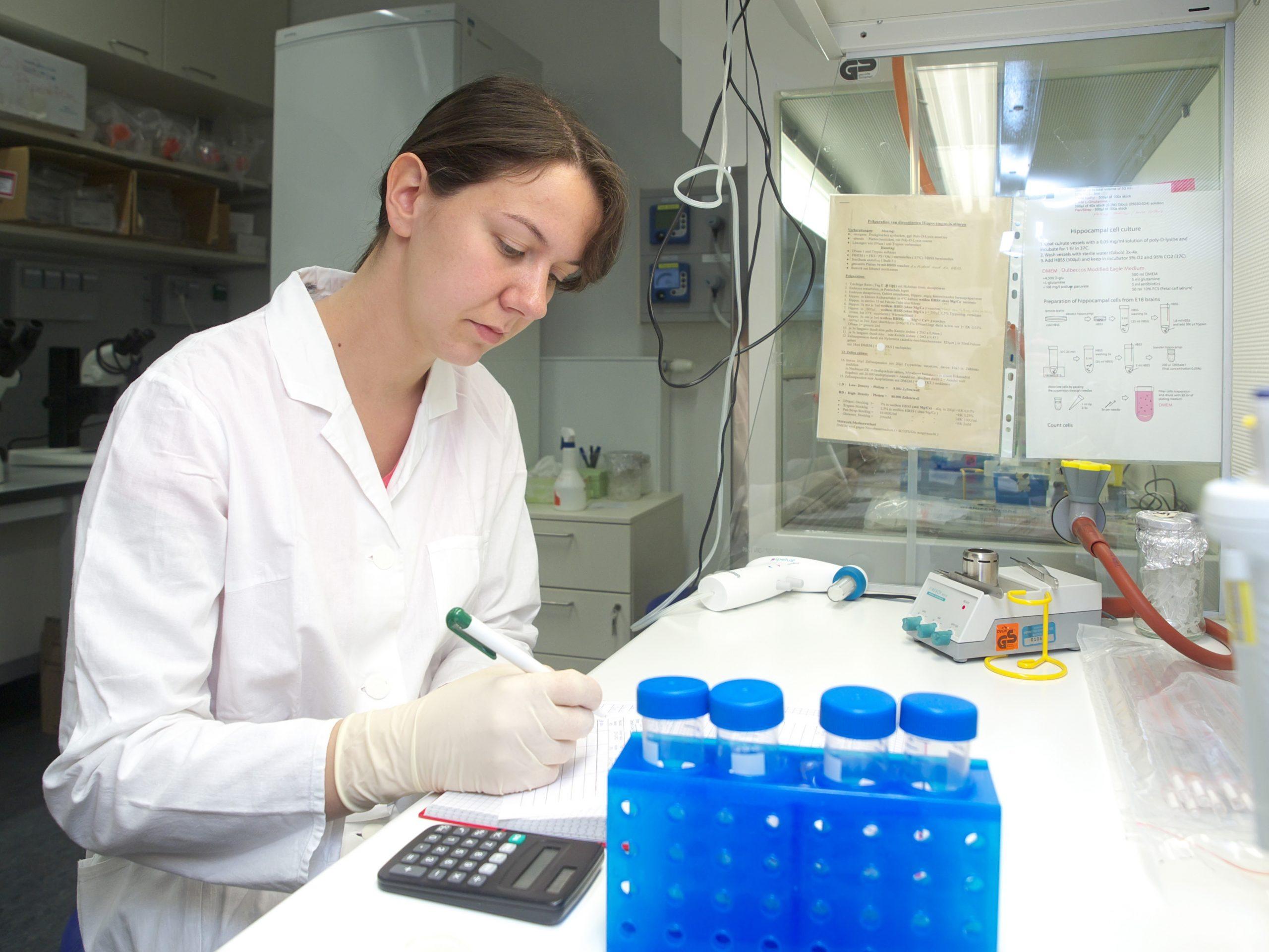 Eine Forscherin im Labor dokumentiert Ergebnisse; Genehmigungsverfahren